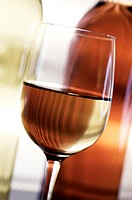 Close-up of a glass of wine in front of two wine bottles