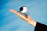 Close-up of a video conference camera on a woman's hand