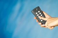 Close-up of a woman's hand holding a remote control