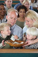 Family in Church Putting Money in Offering Plate