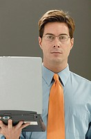 Man holding laptop computer, portrait.