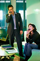 Man and woman talking on cellular phones