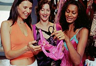 Three women shopping in store, smiling