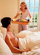 Woman Serving a Man Breakfast in Bed