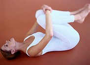 Woman Clasping Her Knees in a Yoga Pose
