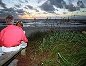 Senior couple watching sunset on beach, rear view
