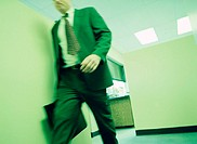 Businessman walking in office, mid section (blurred motion)