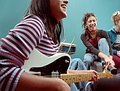 Three teen girls (14-16) smiling, girl in foreground playing guitar