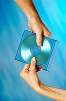 Close-up of a man and a woman´s hands holding a compact disk