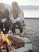 Young man and woman roasting marshmallows over campfire