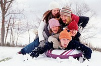 Five young people piled on top of inner tube on snow