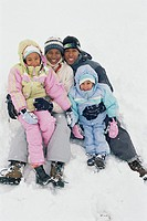 Parents and daughters (3-7) sitting in snow, portrait, winter