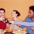 Group of young adults raising toast at dinner party, smiling