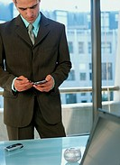 Businessman using personal digital assistant in office