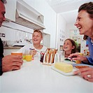 Family having breakfast at kitchen table, laughing, close-up
