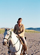 Woman riding horse on beach, Washington, USA (selective focus)