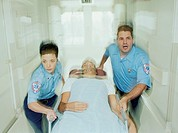 Emergency medical technicians wheeling on patient in stretcher