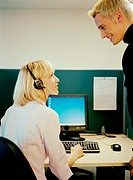 Young man talking to colleague in call centre