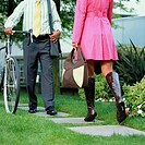 Businessman with bike walking past young woman, low angle view