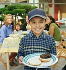 Boy (6-8) holding plate with hamburger, family barbecue (focus on boy)