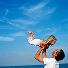 Father holding up daughter (2-4) on beach, smiling, close-up