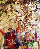 Boy and girl (8-10) throwing autumn leaves in air (blurred motion)