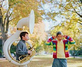 Girl (8-10) standing beside boy (8-10) playing tuba, plugging ears