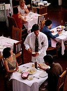 Waiter serving patrons in restaurant, elevated view