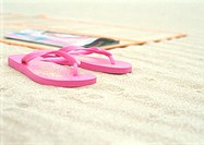 Pink flipflops next to beach mat on beach
