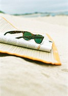Sunglasses and newspaper on beach mat