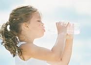 Little girl drinking water from bottle