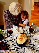 Grandmother Hugging Granddaughter at the Table