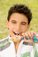 Portrait of a boy eating a chicken drumstick