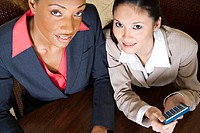 Portrait of two businesswomen smiling holding a calculator