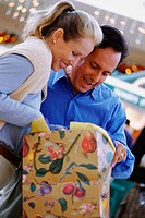 Couple looking into floral shopping bag