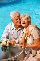 Couple drinking champagne, poolside