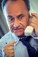 Older man in tie on telephone