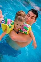 Father playing with girl in pool