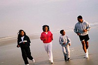 Family of four on jogging on beach