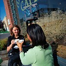 Women Drinking Lattes Outside of Cafe