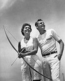 Man standing beside woman who is holding bow and arrow