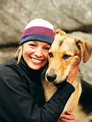 Woman wearing knit cap, hugging dog, portrait