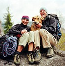 Two female hikers sitting with dog, laughing, portrait