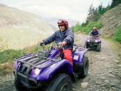 Couple riding ATV´s on dirt road in mountains, blurred motion