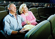 Mature couple watching movie in theater, laughing