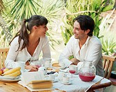 Young couple talking over breakfast outdoors
