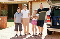 Family standing in driveway beside car loaded with suitcases, portrait