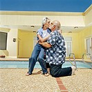 Senior couple kissing by swimming pool