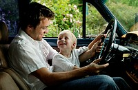 Boy (3-5) sitting with man in car, both holding steering wheel