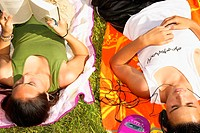 Teen siblings (14-16) lying in grass, reading and listening to music
